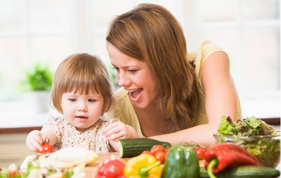 Mother and daughter in kitchen making a salad smiling